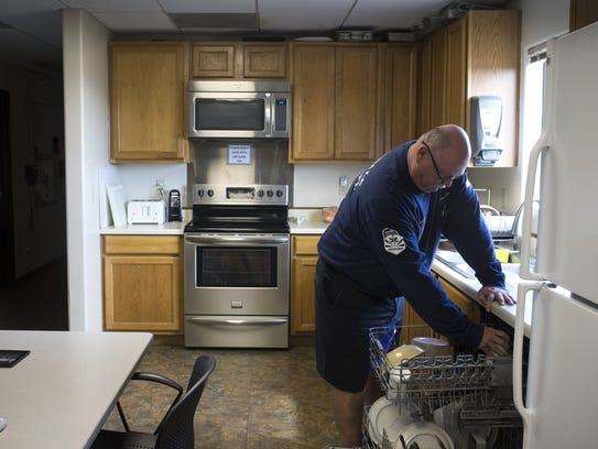 Firefighter Dave Martin puts a dish in the dishwasher