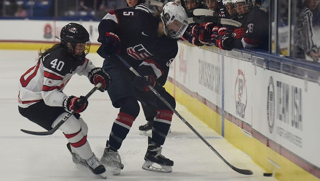Team USA's Megan Keller (5) moves the puck behind Canada's Blayre Turnbull (40) Saturday at USA Hockey Arena in Plymouth.   JUNFU HAN | STAFF PHOTOGRAPHER