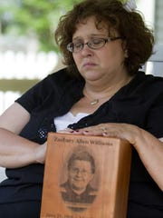 A year after the Joplin tornado, Tammy Niederhelman holds an urn with the remains of her son Zach Williams, who was killed in the May 22, 2011 tornado.