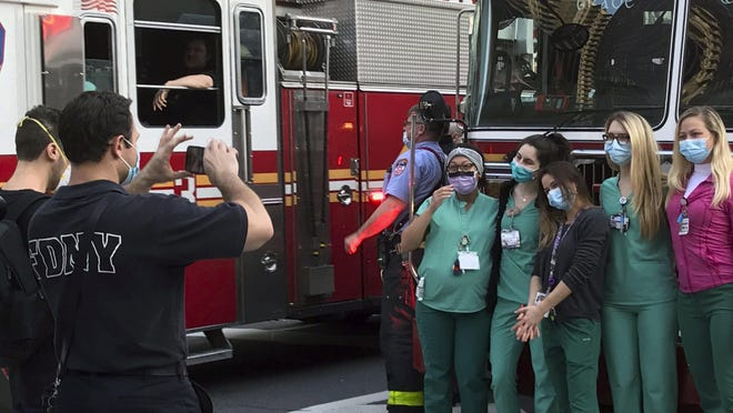 NYU Langone Medical Center staffers ask a New York City firefighter to photograph them in front of the firetrucks gathering for the 7 p.m. appreciation clap for health care workers amid the coronavirus pandemic, Saturday, May 2, 2020, in New York.