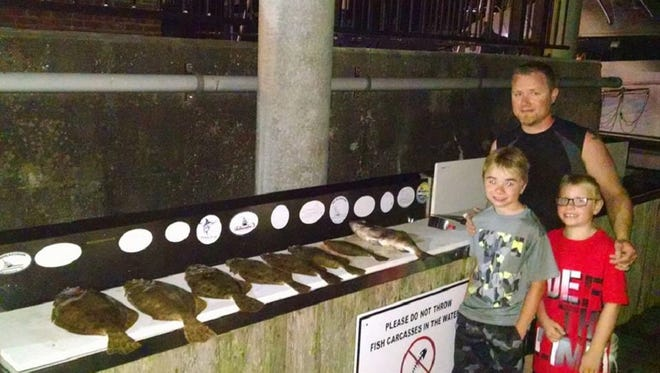 A happy family after a night of flounder gigging with local inshore guide Captain Mike Gasparino.
