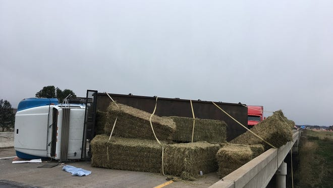A flatbed truck lies on its side with hay bales around it after a crash on State 29 in Clark County Wednesday afternoon.