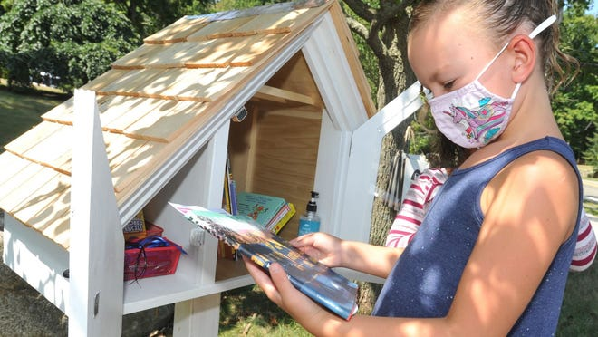 Maeve Russo, 6, looks at a book she selected from the Little Free Diverse Library at the home of Conor and Emily Doherty on Country Way in Scituate, Sunday, Aug. 23, 2020. Tom Gorman/For The Patriot Ledger