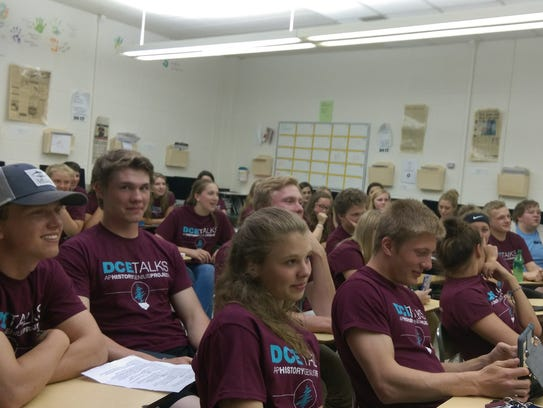 Students listen to a presentation by one of their classmates.
