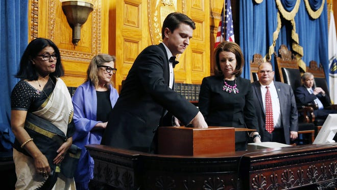 In this December 2016 photo, Massachusetts elector Jason Palitsch, center, takes ballots from the ballot box to be counted as fellow electors Nazda Alam of Weston, left, and Marie Turley, second from left, observe.