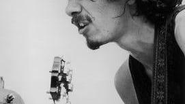Carlos Santana plays guitar at Woodstock.