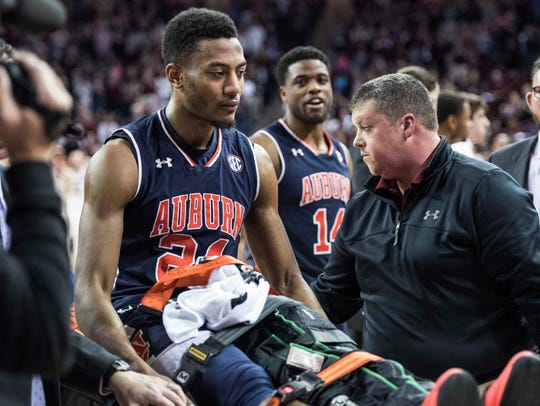 Auburn forward Anfernee McLemore (24) is carted off