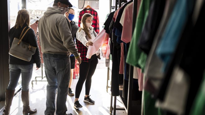 """Mackenzie Maxedon, center, looks through the custom designed shirts on display at Reverie Apparel along with her mother and father, Jake and Brandi Maxedon, and fiancé, Noah Meyer, during Small Business Saturday at the shop on East Adams Street, Saturday, November 28, 2020, in Springfield, Ill. """" With everything going on it's a little more important to support the local small businesses for sure,"""" said Jake Maxedon of the family's trip to downtown Springfield to shop on Small Business Saturday."""