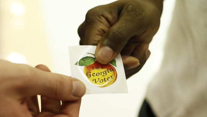 """A voters picks up a, """"I'm a Georgia Voter,"""" sticker after voting at Clarke Central High School in Athens, Ga., on Tuesday, Nov. 3, 2020."""