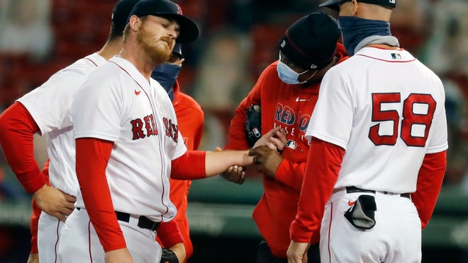 A trainer examines the wrist of pitcher Dylan Covey, left, during the sixth inning of a baseball game against the New York Yankees, Saturday, Sept. 19, 2020, in Boston. Covey stayed in the game.