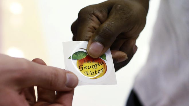 "A voters picks up a, ""I'm a Georgia Voter,"" sticker after voting at Clarke Central High School in Athens, Ga., on Tuesday, Nov. 3, 2020."