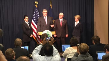 Eric Holcomb speaks as Gov. Mike Pence and Lt. Gov. Sue Ellsperman look on. To Holcomb's right is his wife, Janet.
