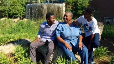 Carole Curry, retired educator and distinguished volunteer, smiles for a photo with Rickards graduate Tyrone Crawford Jr. (left) and Joshua Purcell, who is entering the seventh grade this year (right).