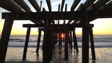 The damaged Ocean Grove Pier at sunrise several days after Hurricane Sandy struck.