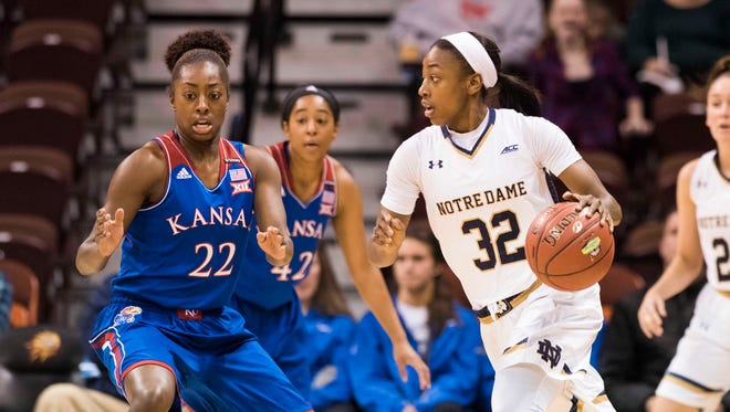 Notre Dame Fighting Irish guard Jewell Loyd (32) dribbles the ball as Kansas Jayhawks guard Chayla Cheadle (22) defends during the first half at Allen Fieldhouse.