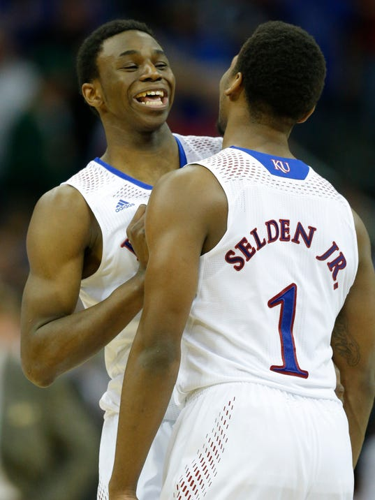 Kansas guard Andrew Wiggins, left, talks with Kansas guard Wayne Selden, Jr. (1) during overtime of an NCAA college basketball game against Oklahoma State in the quarterfinals of the Big 12 Conference men's tournament in Kansas City, Mo., Thursday, March 13, 2014. Kansas defeated Oklahoma State 77-70 in overtime. (AP Photo/Orlin Wagner)