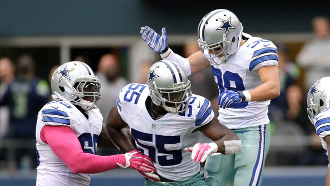 Dallas Cowboys linebacker Rolando McClain (55) celebrates with teammates after he intercepted a pass against the Seattle Seahawks on Sunday, Oct. 12, 2014, in Seattle.