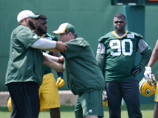 Green Bay Packers lineman B.J. Raji watches as defensive line coach Mike Trgovac teaches technique during Organized Team Activities at Clarke Hinkle Field May 28, 2015.