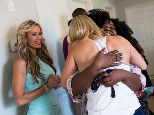 Guiseline Fortune-Brumaire hugs Katie Werchek during the reveal of her family's new Habitat for Humanity home in Golden Gate Estates on Thursday, June 29, 2017. A team of Realtors and designers, including Werchek, donated furniture and their services to make the house a home for the family.