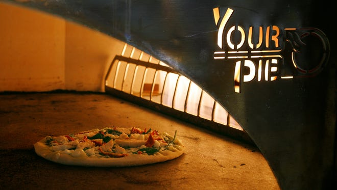 A pizza bakes in a wood-fired oven at Your Pie.