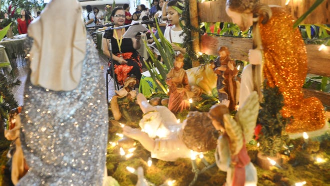Chamorro language teacher, Senora Ruth Mendiola, seated left, and Chamorro studies student, Maria Cruz, sing the classic Chamorro song, Fanmatto, during the Puengen Minagof Noche Buena celebration at the University of Guam on Dec. 6 2014. The event featured a bilens, or nativity scene, decorating contest; a parol, or Filipino lantern, making contest; bonelos, or fried donut, tasting as well as other desserts; Chamorro poetry slam performances and a stage performance in Chamorro depicting the birth of Christ. A donation of one dollar was collected as a vote during the belen contest.