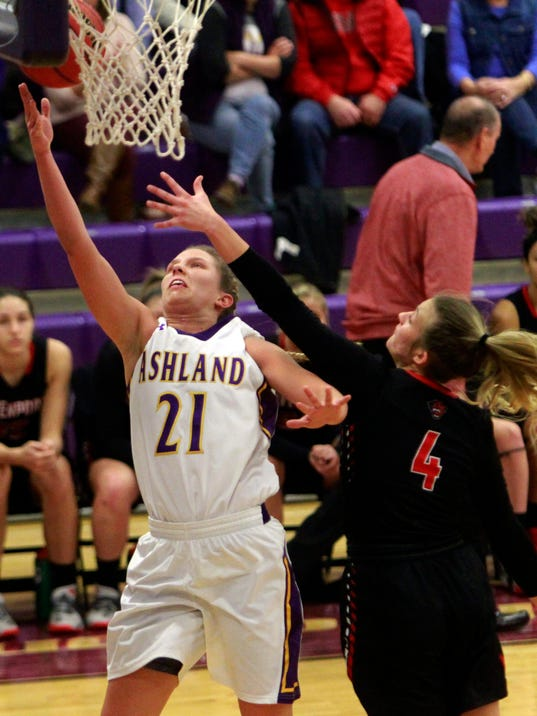 In this Dec. 9, 2017 photo, Ashland University's Jodi Johnson (21) drives in for a layup against Davenport University's Hannah Wilkerson (4) in the second quarter during an NCAA women's basketball game at Kates Gymnasium in Ashland, Ohio. On a small-town campus amid a patchwork of northeastern Ohio farm fields, Ashland University has quietly built a women's college basketball juggernaut. (Tom E. Puskar/The Times Gazette via AP)