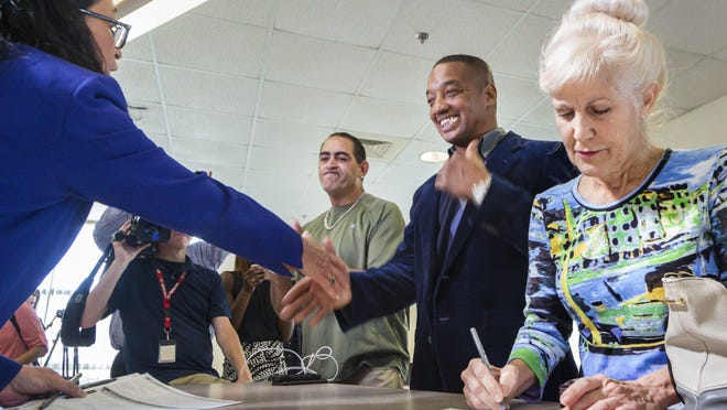 Former Palm Beach County Supervisor of Elections Susan Bucher congratulates Anthony Ray Hoskins of Boynton Beach as former felons register to vote at the elections headquarters on Jan. 8, 2019, following the passage of Amendment 4.