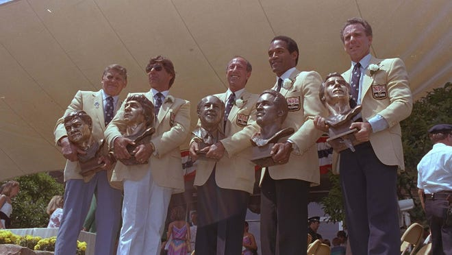 The five enshrines into the Pro Football Hall of Fame pose with their bronze busts in front of the shrine after induction ceremonies Saturday, Aug. 3, 1985 in Canton, Ohio.  They are, left to right, Frank Gatski, Joe Namath, Pete Rozelle, O.J. Simpson and Roger Staubach.   (AP Photo)