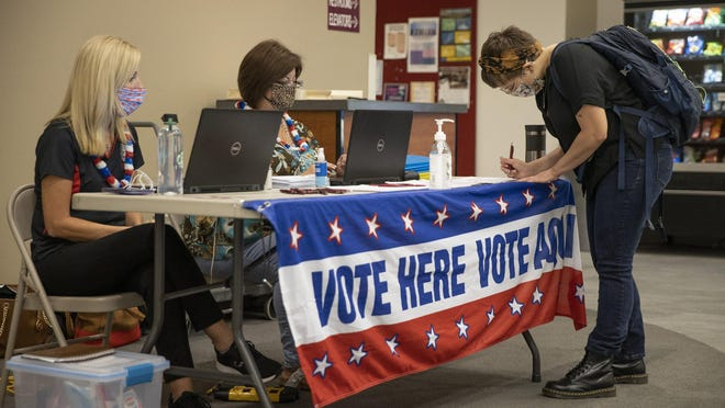 Hays County Elections Administrator Jennifer Anderson, left, and Virginia Flores, the county's chief voter registration and election clerk, help student Victoria Grist register to vote at Texas State University in San Marcos on Sept. 22.