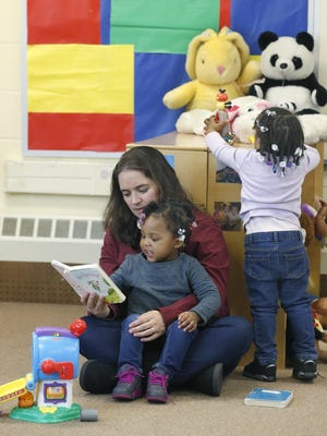 Childcare worker Jessica Zambuto reads a book with Zorri David, 2, while behind Kali Tate, 2, plays with toys at Generations Child Care in Gates.
