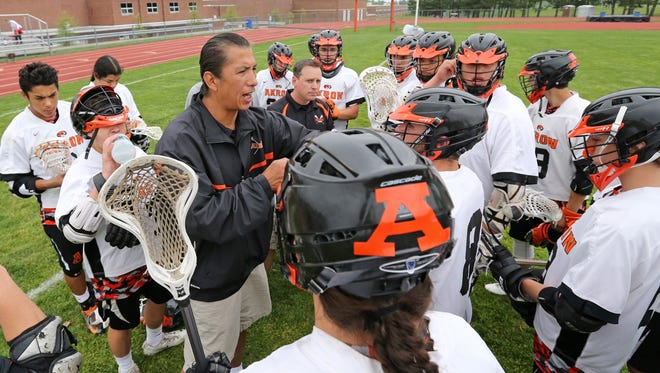Akron assistant coach Gary Sundown addresses the team for which his son, Larson, plays.