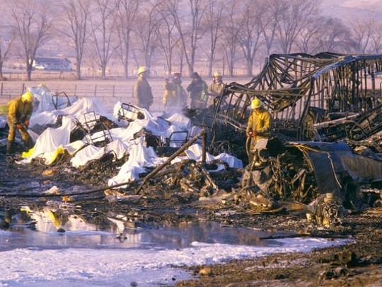 Firefighters water down the wreckage of Galaxy Flight