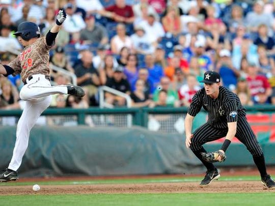 Virginia's Kevin Doherty (28) runs over the ball as Vanderbilt's Will Toffey waits to field the ball during the third inning in the College World Series on June 22, 2015.