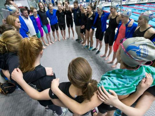 Carmel High School swimmers and coaches huddle up before the start of the IHSAA girls high school state championships at the IUPUI Natatorium Saturday.