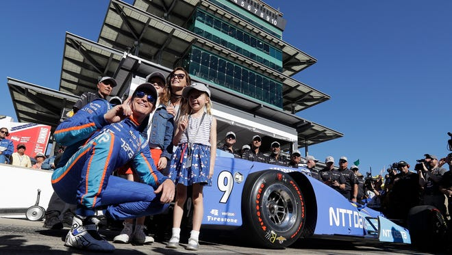 Scott Dixon poses  with his wife, Emma, and children, Poppy and Tilly, after winning the pole.