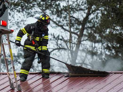 Firefighters work on the roof as fire crews battle
