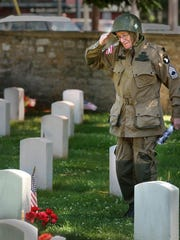 Ralph Manley, a paratrooper in the 101 Airborne Division who jumped on D-Day, salutes the grave of his twin brother, Roland Manley, who lost his life at the age of 19 while on a mission with the 82nd Airborne Division during WWII.