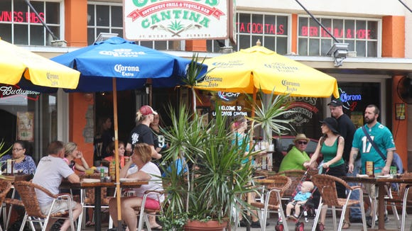 Visitors to downtown Fort Myers go about their business