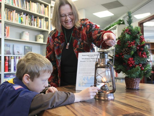 Sharon Strohmaier of Iowa Religious Media Services in Urbandale watched Boy Scout Jacob Storey of Dallas Center light a candle from the Peace Light lantern at IRMS in 2011.