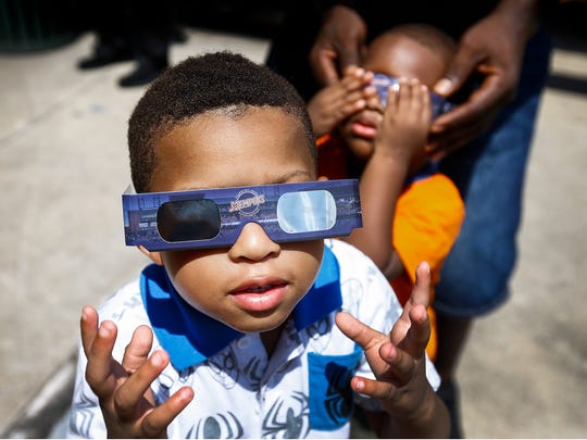 Jermaine Curtis, 4, takes a peek at the solar eclipse as cousin Dante Elzey, 2, (right) gets fitted with protective glasses during the Memphis Redbirds Eclipse Party during a break in action Monday afternoon.