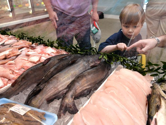 Predators fan Caleb Daniel, 5, of Franklin picks out a catfish at Little's Fish Market on Friday, May 4, 2018. Daniel will help throw to a catfish on the ice before Preds game on Saturday. While Daniel lived at Vanderbilt Children's waiting for a heart transplant, he would throw his stuffed catfish off the bed.