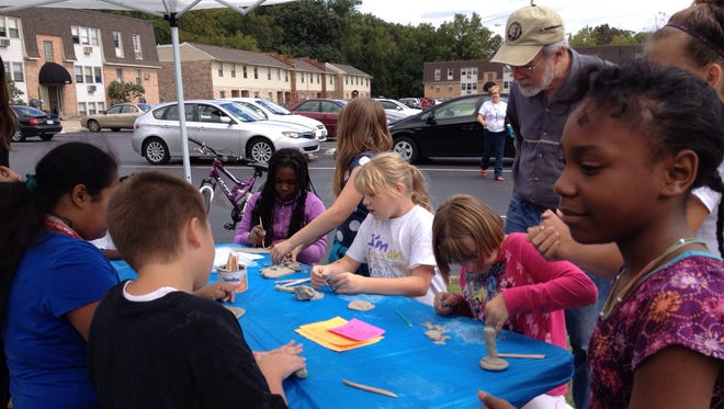 Volunteer Jeff Arnold of Cincinnati Friends Meeting supervises children modeling with clay at 2014 at Artsy Fartsy Saturdays' Community Art Day.