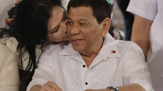 "Philippine President Rodrigo Duterte is kissed by congresswoman Rose Marie ""Baby"" Arenas during the ceremonial signing of 2018 General Appropriations Act and Tax Reform for Acceleration and Inclusion Bill at the Malacanang Presidential Palace in Manila, Philippines on Tuesday Dec. 19, 2017."