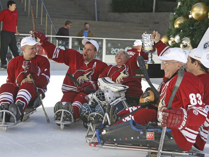 Sled hockey team members skate around the ice during