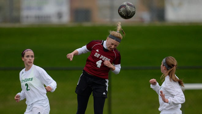 De Pere's Alexis Mashl (4) hits a header during Thursday night's FRCC soccer game at Notre Dame Academy.