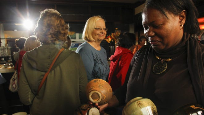 """Cynthia Thomas of Lansing chooses from an array of handcrafted pottery, Oct. 2, 2014, during the 24th annual """"Empty Bowls"""" fundraiser at Troppo in downtown Lansing.  Attendees donated $20 per piece, and soup was served by Food Bank volunteers."""