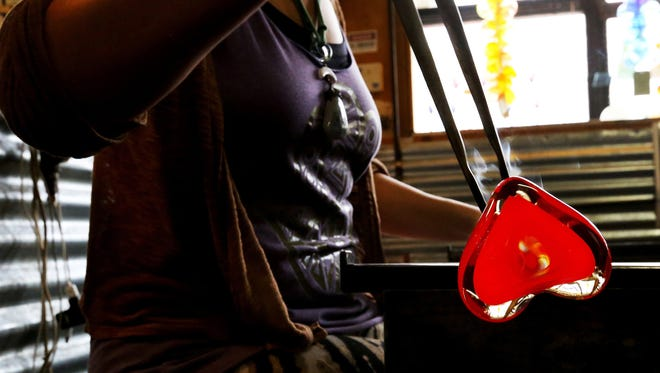 """Amy Crawford works a piece of molten glass she's introduced red into, slowly forming the heart shape. To do this work she says """"is the necessity of being present in the process."""""""