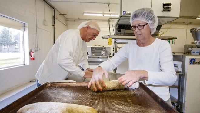 Owner Chris Pinahs and baker Terri Schuldt prepare Artisan Rye bread at StoneBank Baking Co. on Nov. 20, 2017.