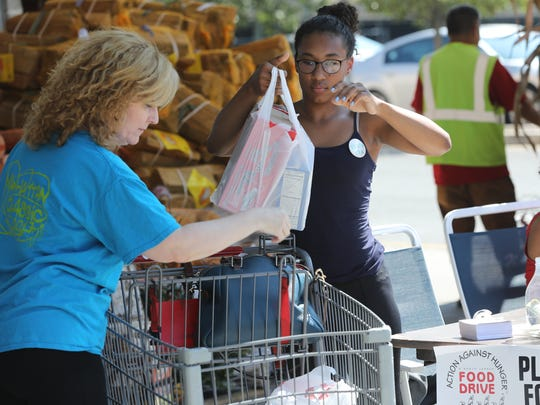 Deirdre Riggsbee, 17, collects food from her mother, Annmarie Lockhart, for the Action Against Hunger Food Drive at the Acme supermarket in Fort Lee in September 2017.