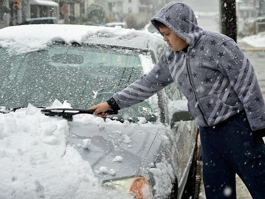 Eliel Soto, 10, brushes snow off his dad's car on Second